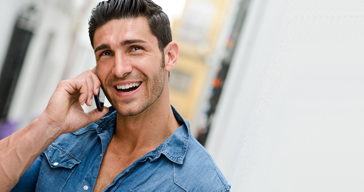 Portrait of good looking man in urban background talking on phone